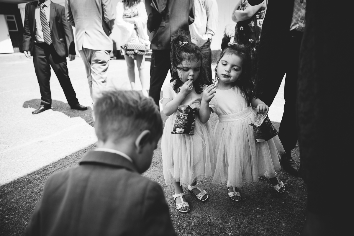 LITTLE GIRLS TWINS EATING CRISPS AT WEDDING
