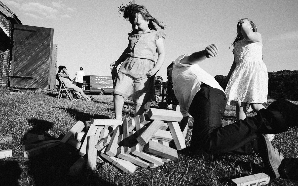 WEDDING PHOTOGRAPHY GIANT JENGA FALLING ON GIRL