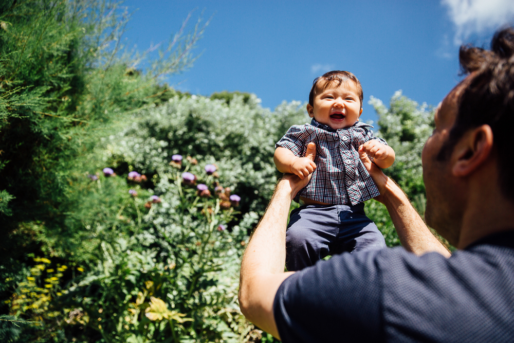 family photography of baby boy thrown in air by father at coastal park, folkestone kent