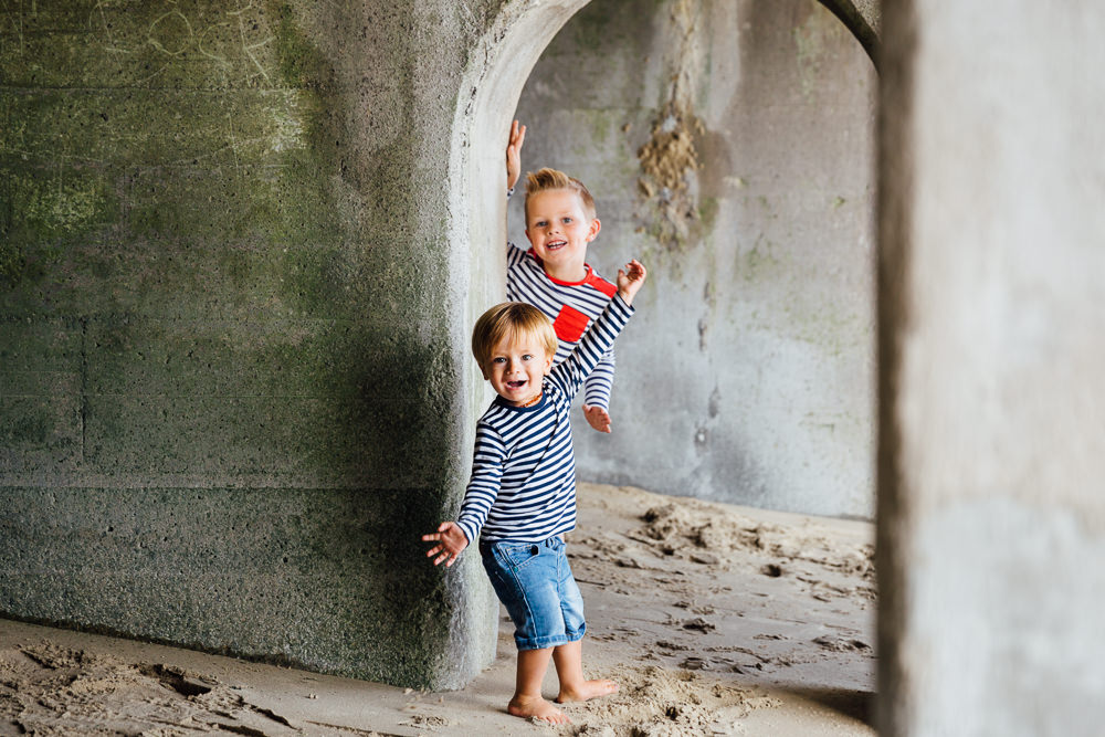 boys playing under arches sunny sands beach folkestone - Family Photographer Kent