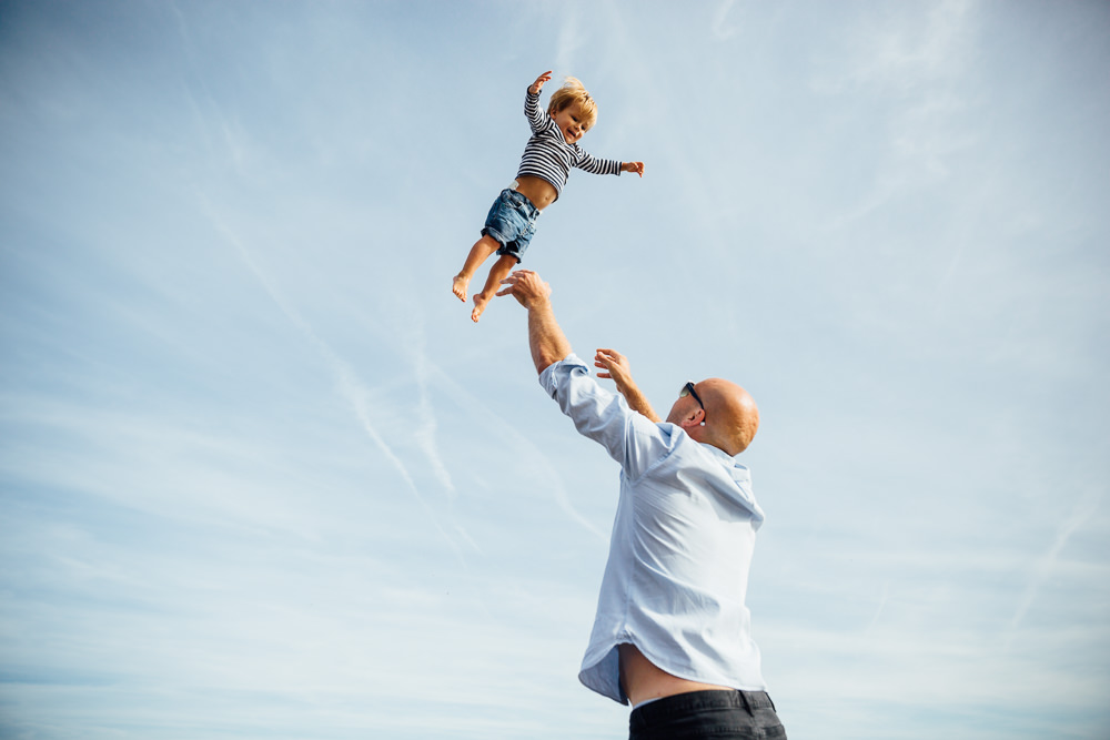 father throwing son in air - Family Photographer Kent