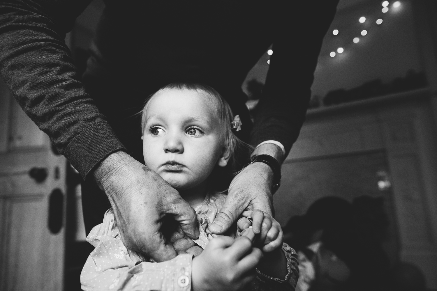 LITTLE GIRL BEING DRESSED BLACK AND WHITE - KENT FAMILY PHOTOGRAPHER