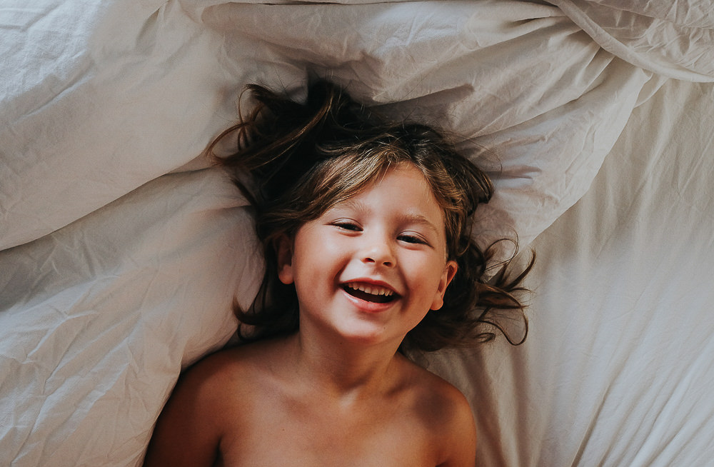 LAUGHING GIRL IN BED - KENT FAMILY PHOTOGRAPHER