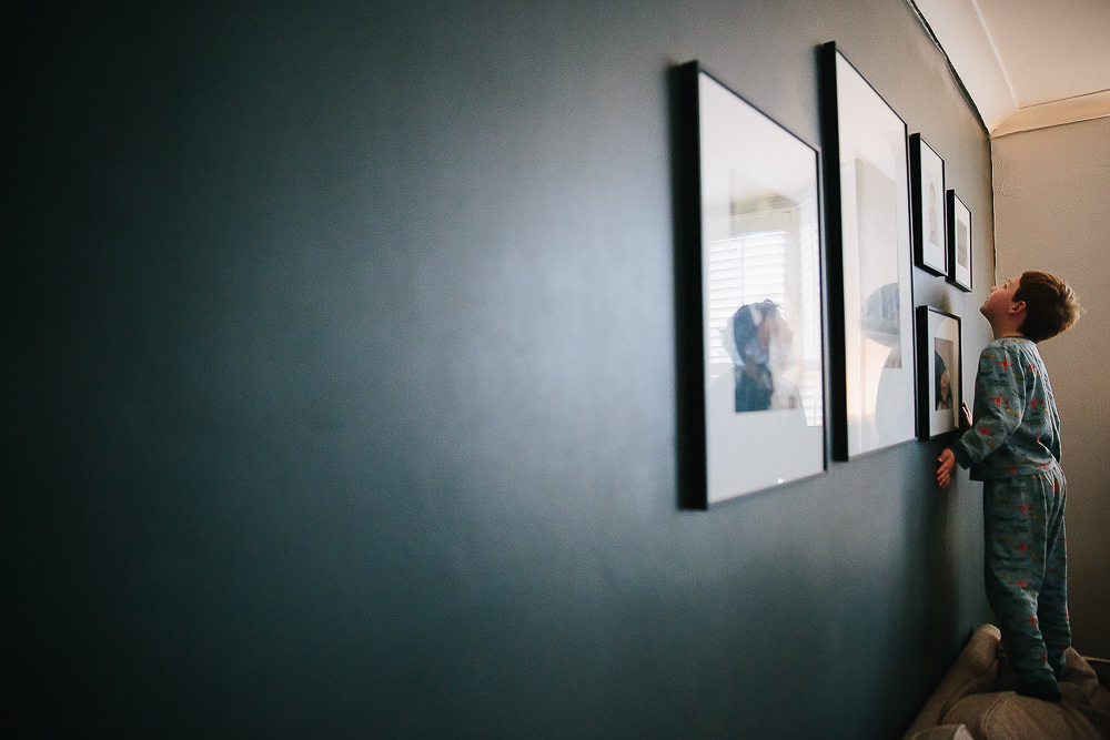 BOY LOOKING AT FRAMED PHOTOS ON WALL - KENT FAMILY PHOTOGRAPHER