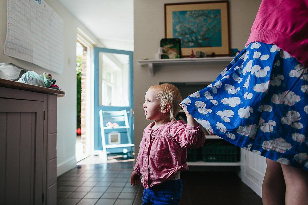 GIRL HOLDING MOTHER'S SKIRT IN KITCHEN - KENT FAMILY PHOTOGRAPHER