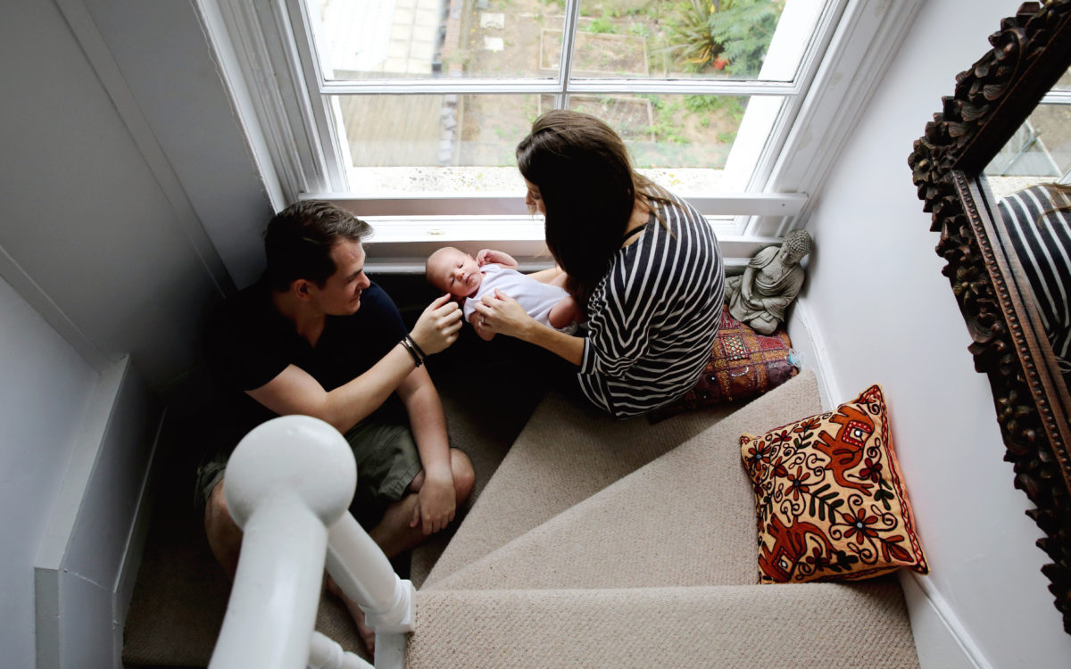 PARENTS WITH NEWBORN BABY SITTING ON STAIRS AERIAL SHOT
