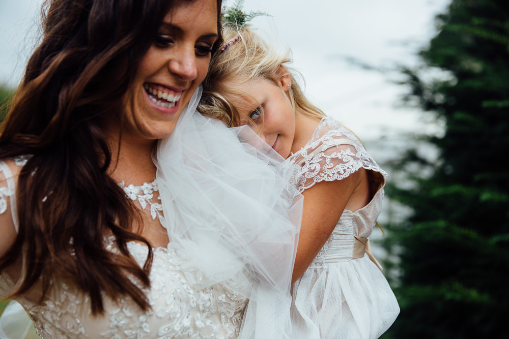 bride carrying flower girl bilsington priory kent wedding photographer