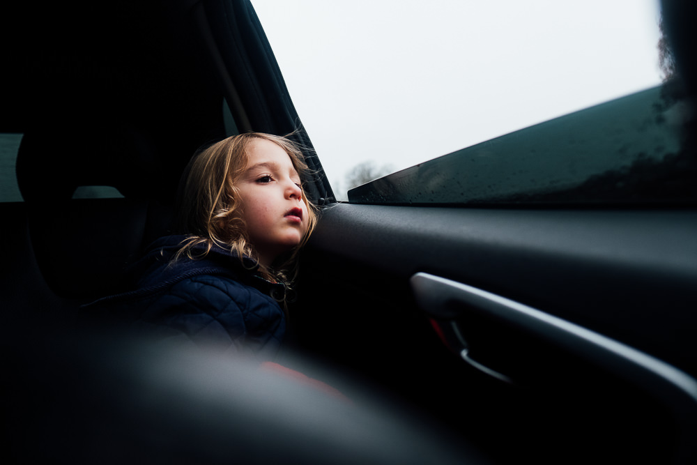 GIRL LOOKING OUT OF CAR WINDOW FAMILY PHOTOGRAPHER KENT AND LONDON RICHMOND PARK