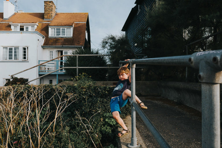 BOY HANGING FROM RAILINGS WHITSTABLE KENT FAMILY PHOTOGRAPHY