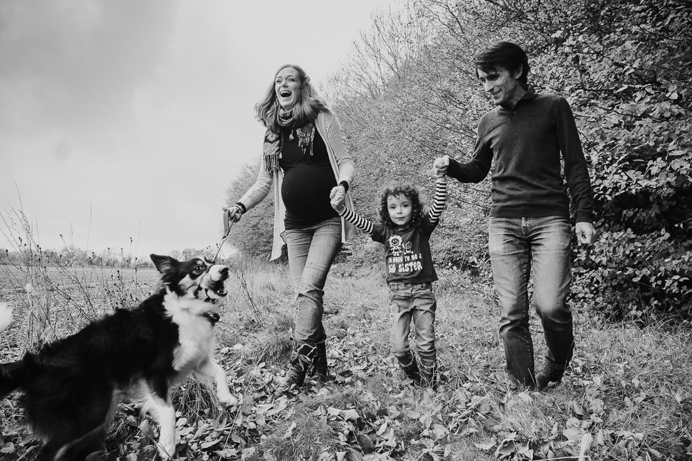 MATERNITY FAMILY PHOTOGRAPHER KENT AND LONDON WALKING IN WOODS BLACK AND WHITE WITH DOG