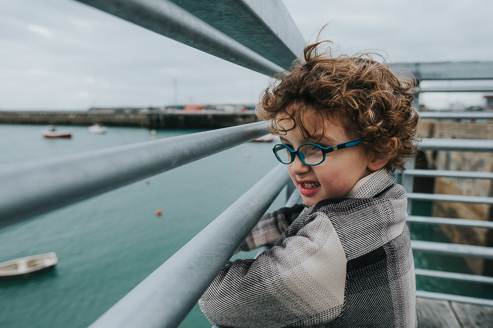 BOY LOOKING THROUGH RAILINGS FOLKESTONE HARBOUR FAMILY PHOTOGRAPHER KENT AND LONDON