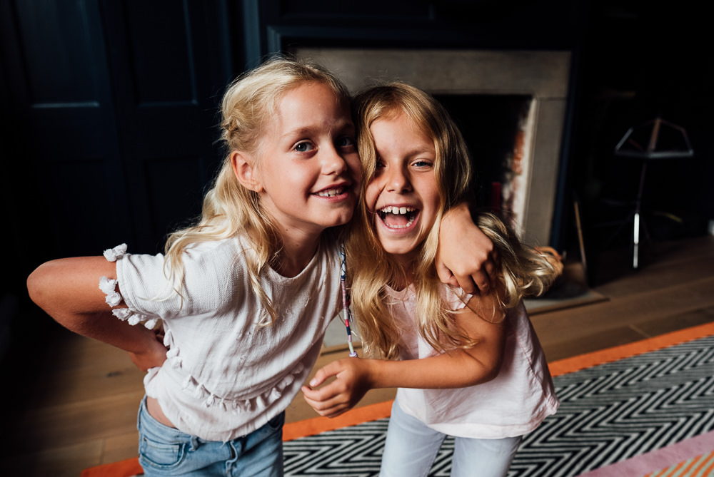 BLONDE SISTERS LAUGHING INDOORS FAMILY PHOTOGRAPHER KENT AND LONDON PORTRAIT CANTERBURY