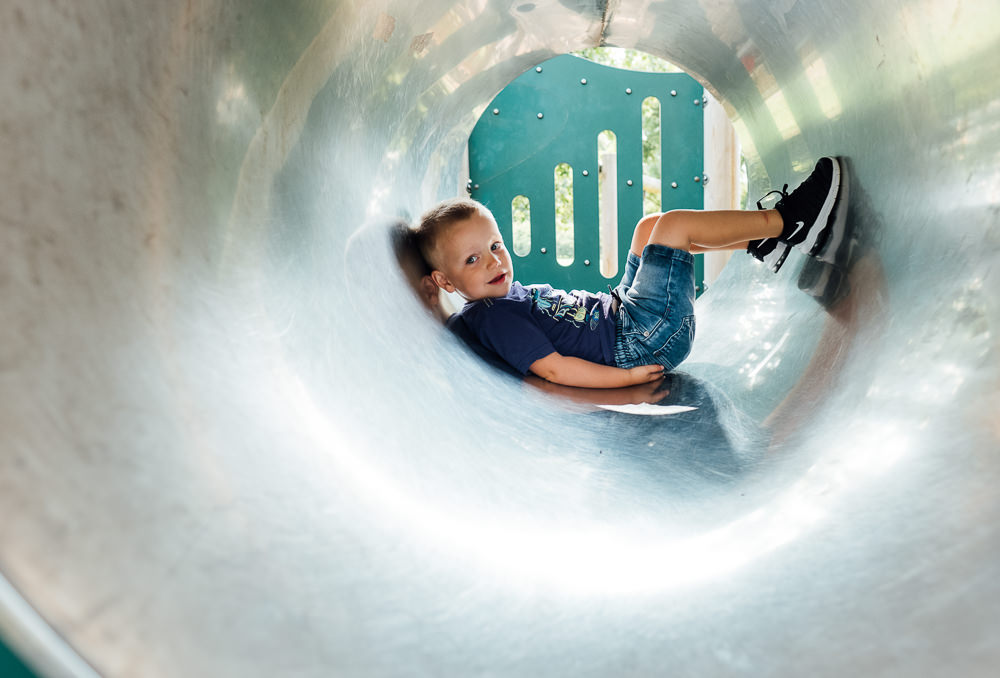 BOY IN PLAYGROUND TUBE EQUIPMENT FAMILY PHOTOGRAPHER KENT AND LONDON