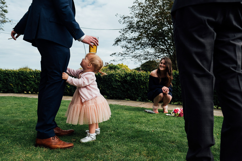 LONDON WEDDING PHOTOGRAPHER PINES CALYX DOVER WEDDING MAN BALANCES PINT ON TOP OF CHILDS HEAD