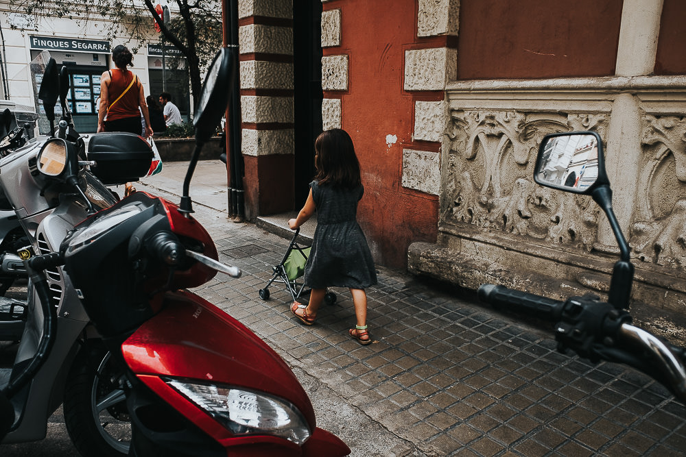 KENT PHOTOGRAPHER BARCELONA SPAIN TRAVEL PHOTOGRAPHY CHILD PUSHING DOLL IN PUSHCHAIR STREET PHOTOGRAPHY
