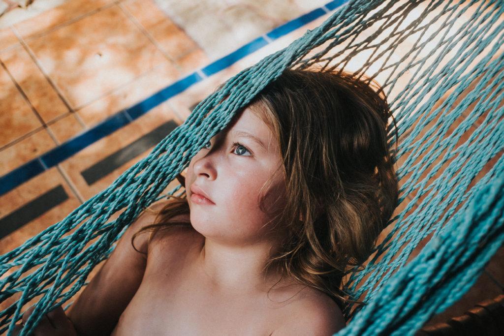 girl child in hammock close up face costa rica blue eyes