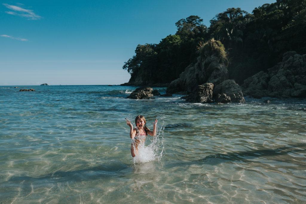 child splashing in waves on beach costa rica parque de manuel antonio