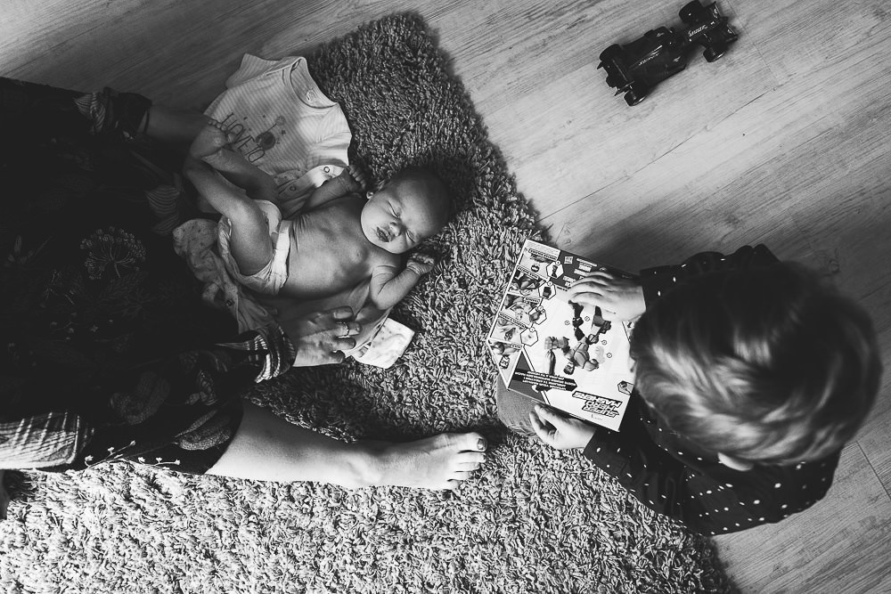 NEWBORN PHOTOGRAPHER LONDON AND KENT BLACK AND WHITE CHANGING BABY ON FLOOR WITH SIBLING