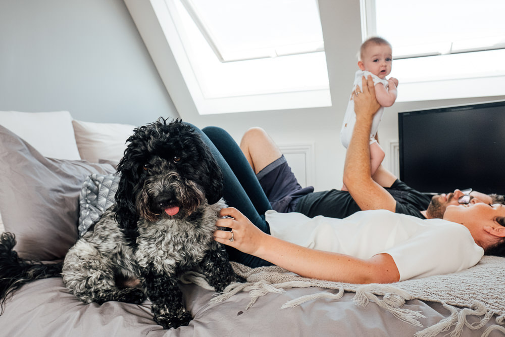 Godstone Surrey Family Photographer parents and dog playing with baby daughter on bed