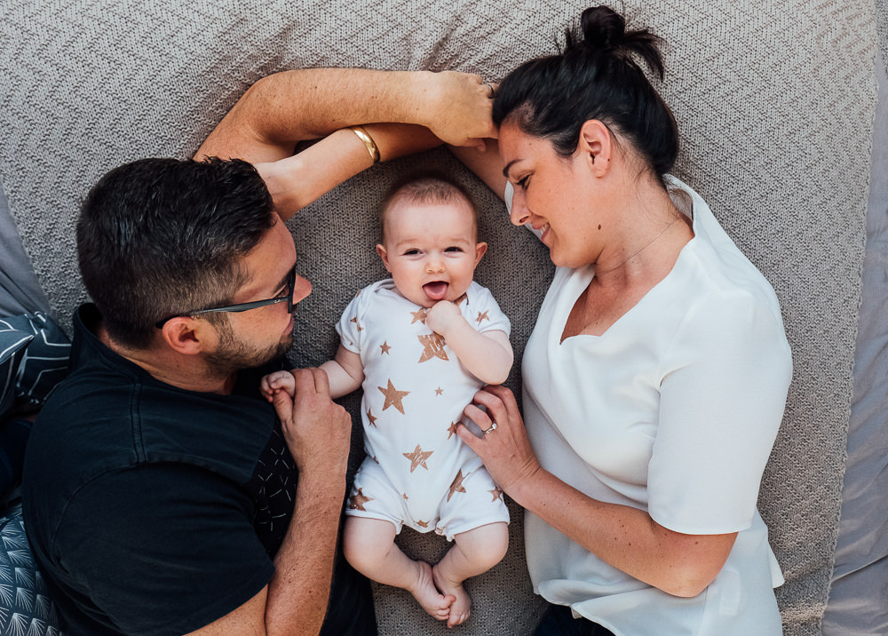 Surrey Family Photographer parents and baby girl on bed smiling