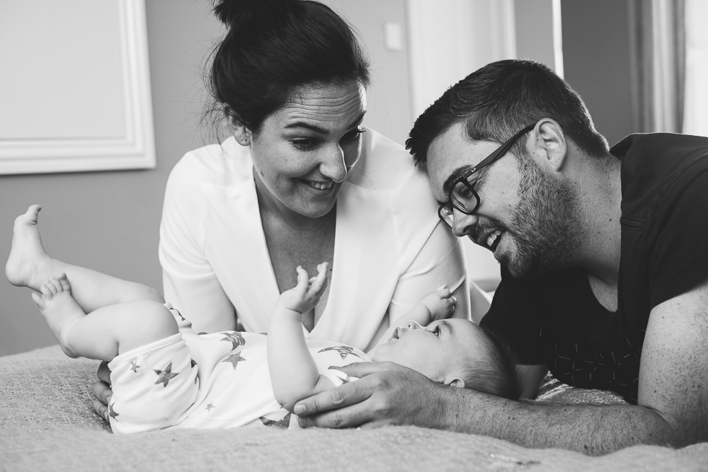Godstone Surrey Family Photographer parents and baby on bed natural light lifestyle portrait laughing black and white
