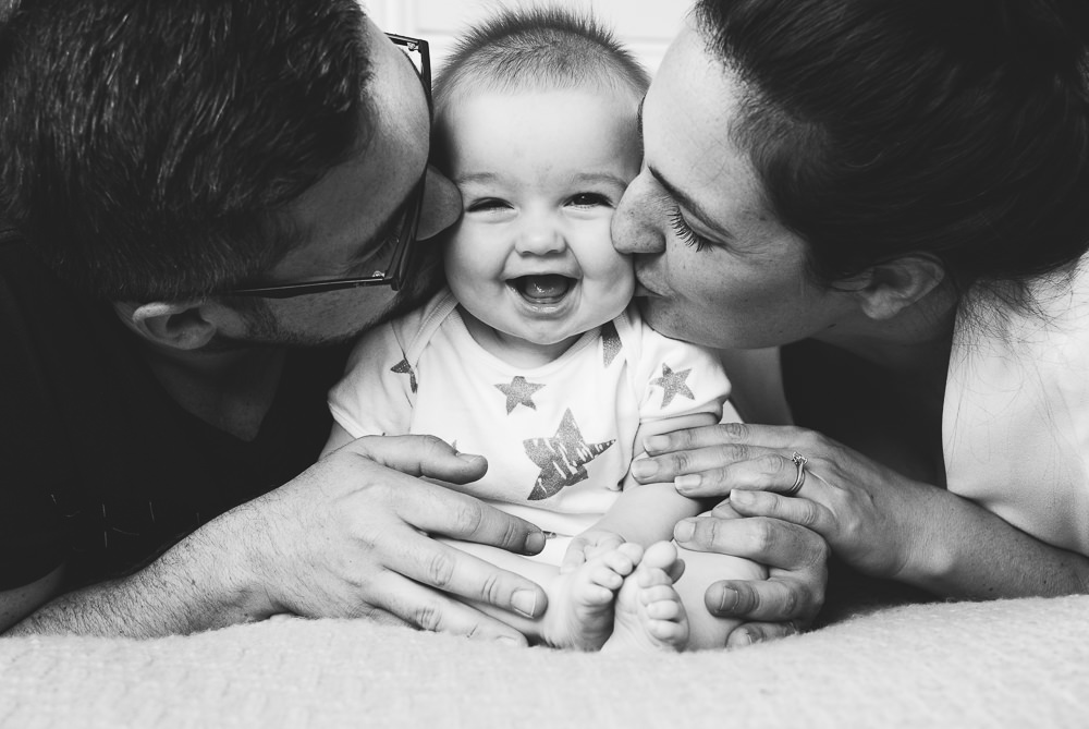 Godstone Surrey Family Photographer parents and baby kissing on cheek on bed natural light lifestyle portrait