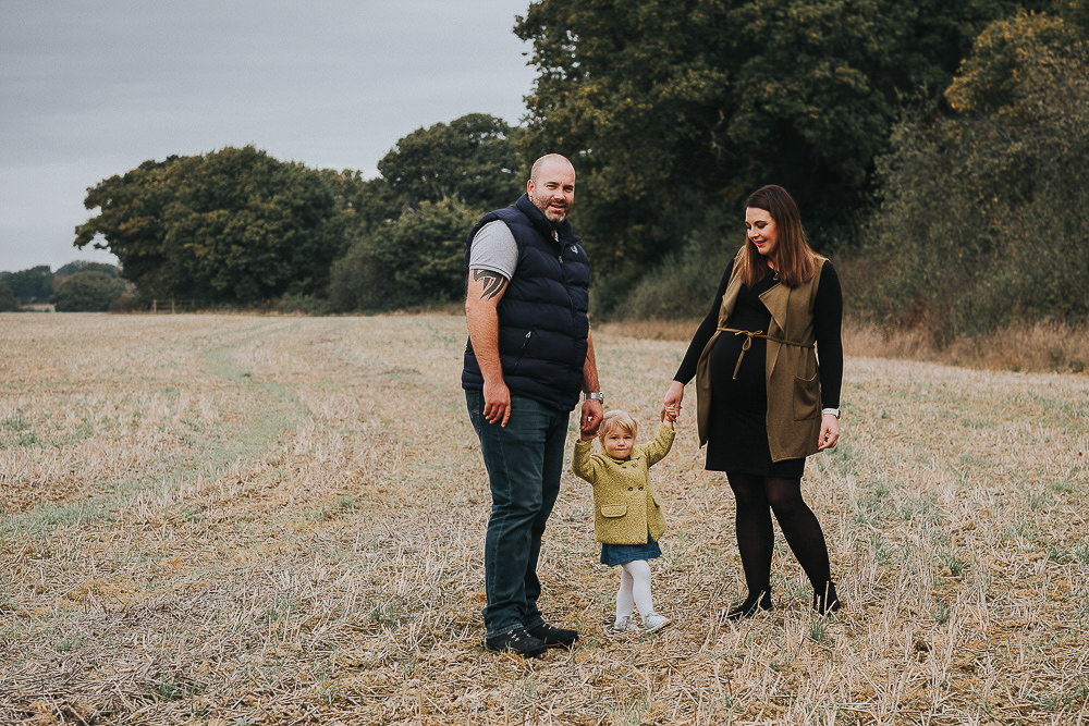pregnant woman with husband and toddler daughter in Kent field