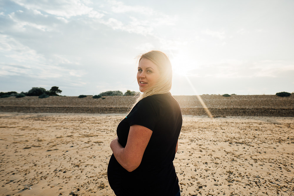 Pregnant woman on beach with sun flare portrait