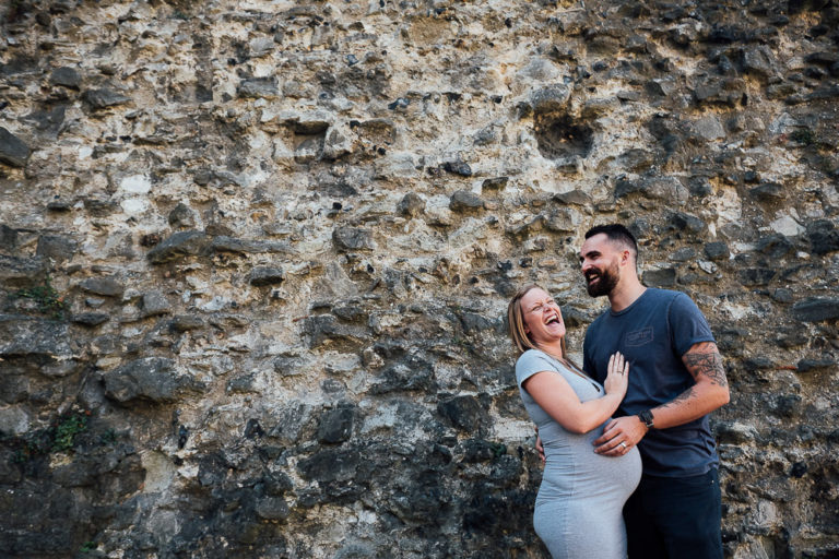 pregnant woman and husband laughing together in front of a wall