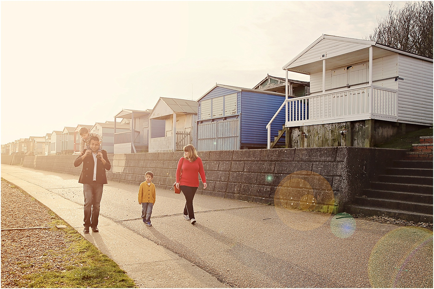 Whitstable beach photography family child family walking in morning light beach huts