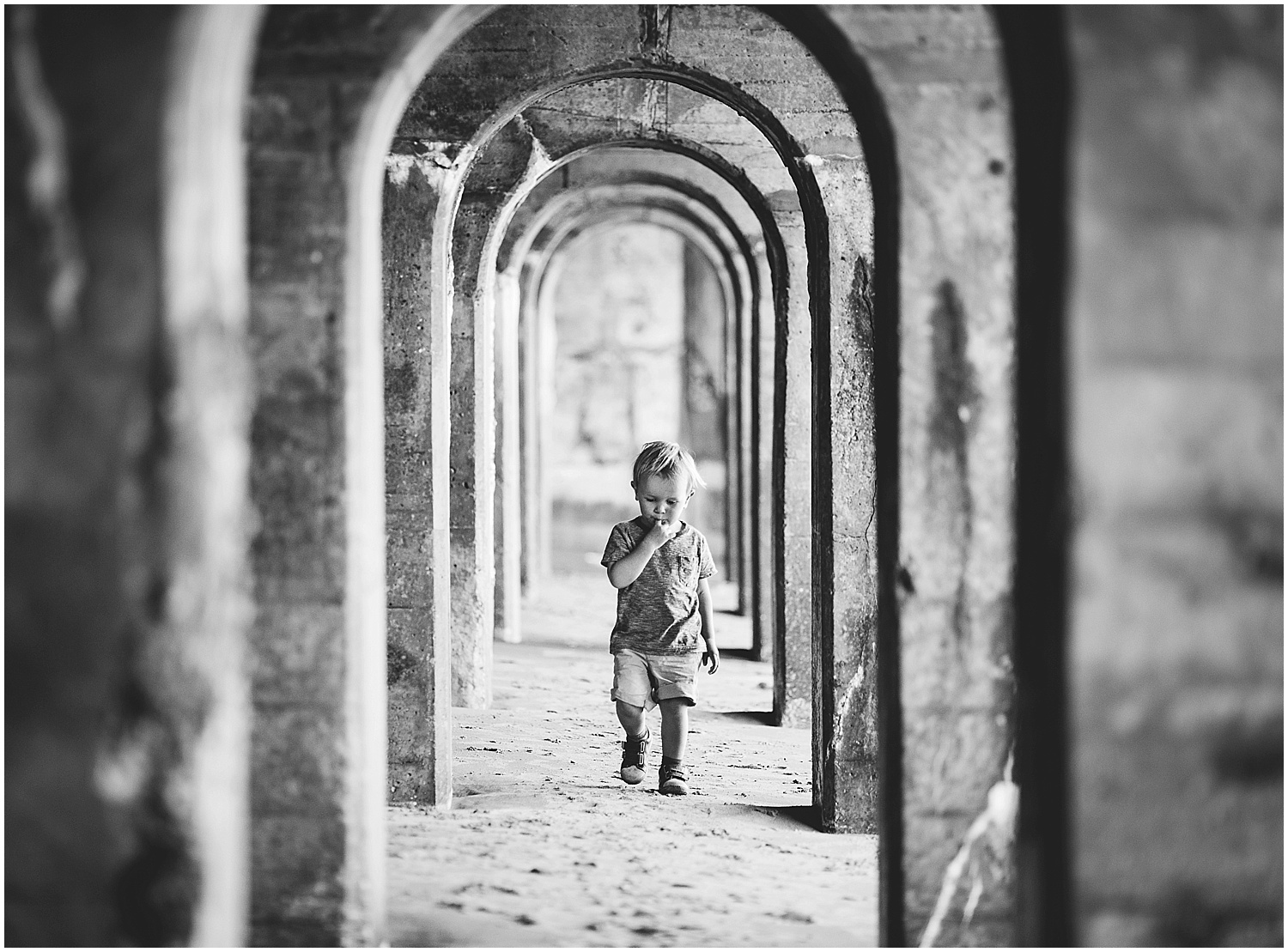 boy underneath arches sunny sands beach folkestone kent family photographer kids
