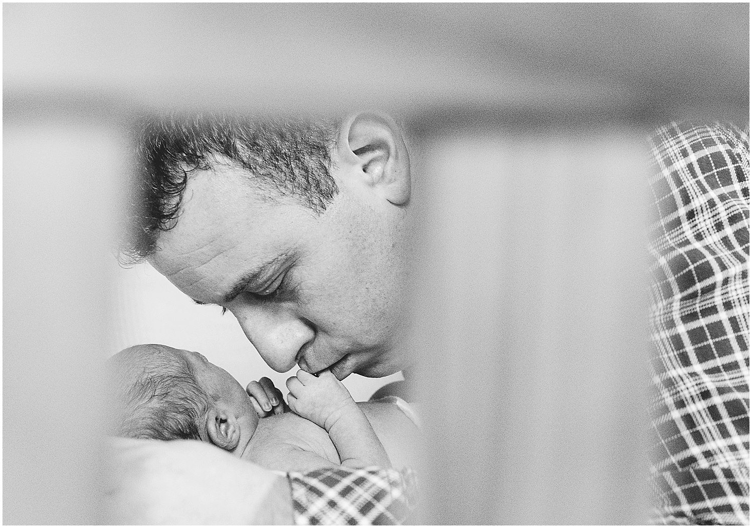 father kissing baby daughter's hand black and white newborn photography at home kent