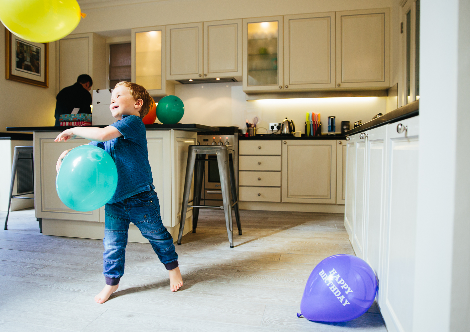 boy in kitchen with balloons birthday party photography