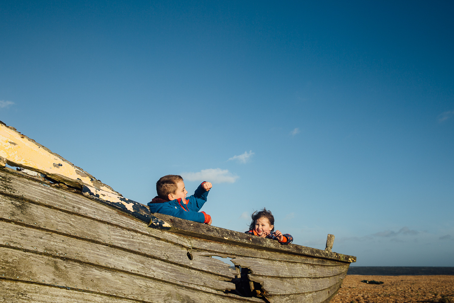 KIDS CHILDREN PLAYING ON DUNGENESS BOATS BEST BEACHES IN KENT FOR PHOTOS