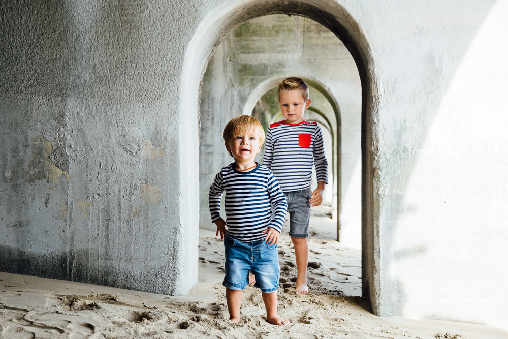 Family photographer Kent - two boys in arches on sunny sands beach folkestone