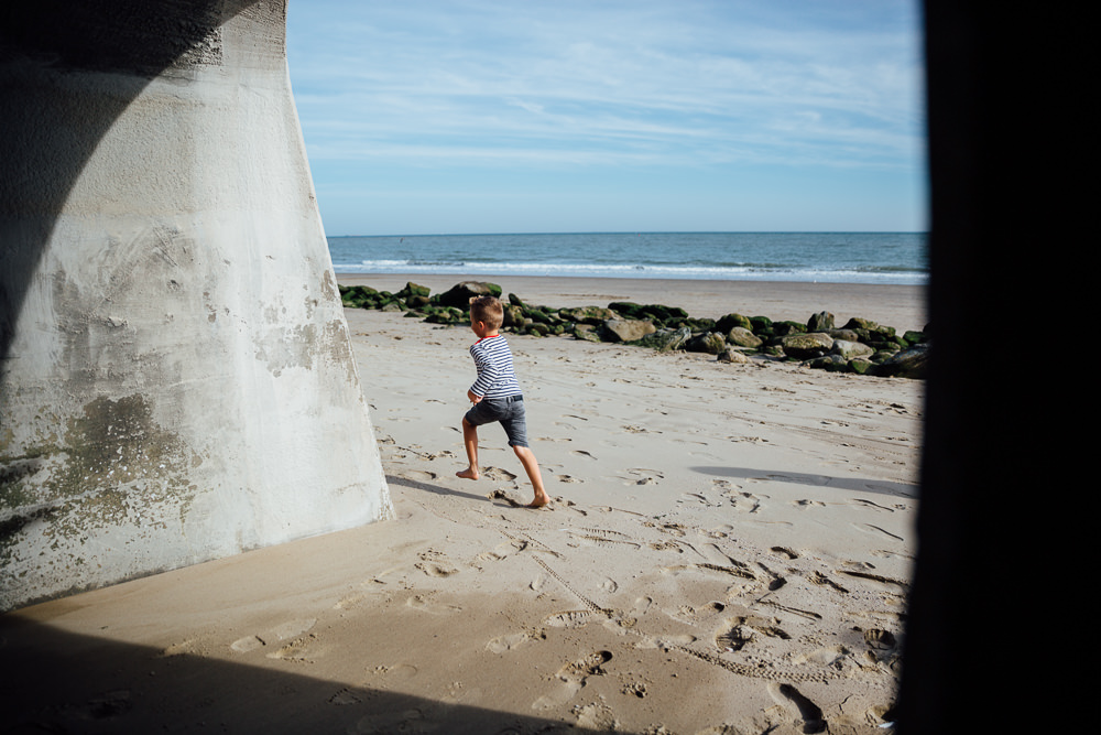 boy playing under arches sunny sands beach folkestone - Family Photographer Kent
