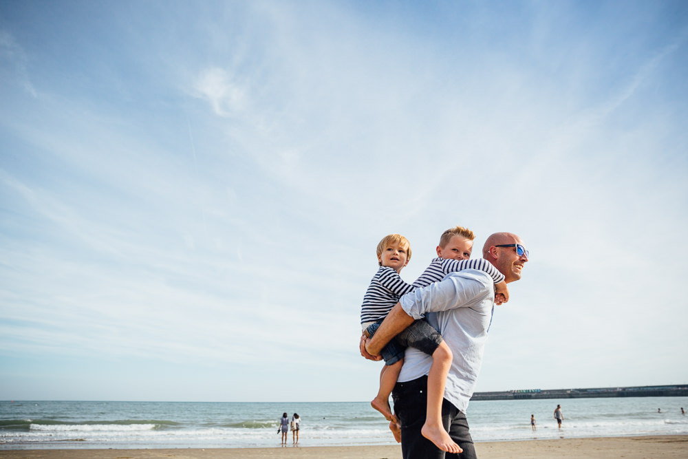 father and sons piggyback sunny sands beach folkestone - Family Photographer Kent