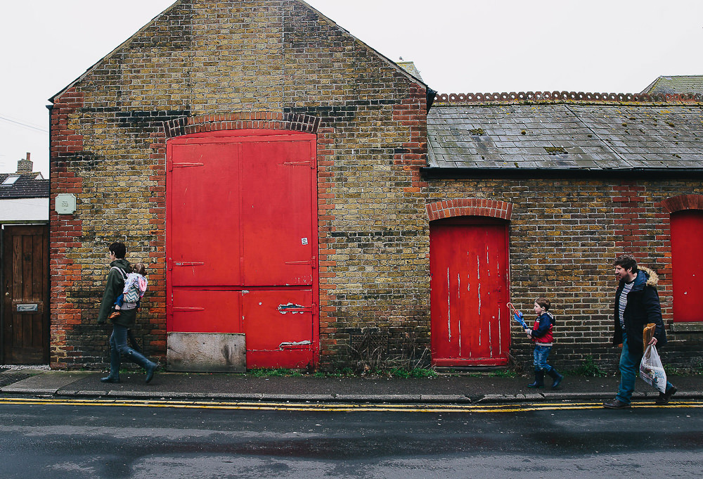 FAMILY WALKING PAST BUILDING WITH LARGE RED DOORS