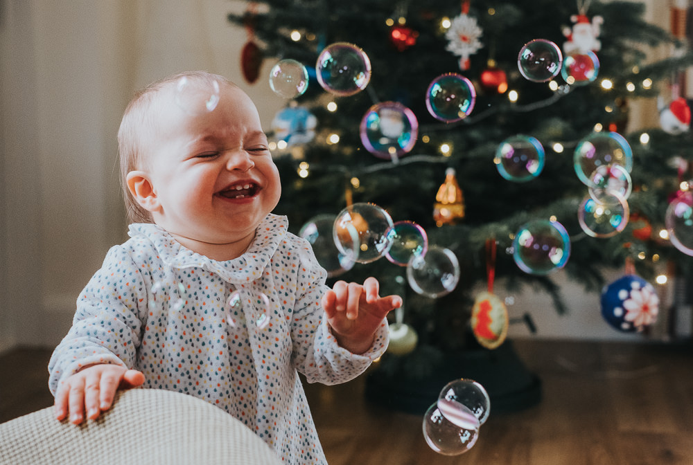 BABY GIRL WITH CHRISTMAS TREE AND BUBBLES FAMILY PHOTOGRAPHER KENT AND LONDON SURREY