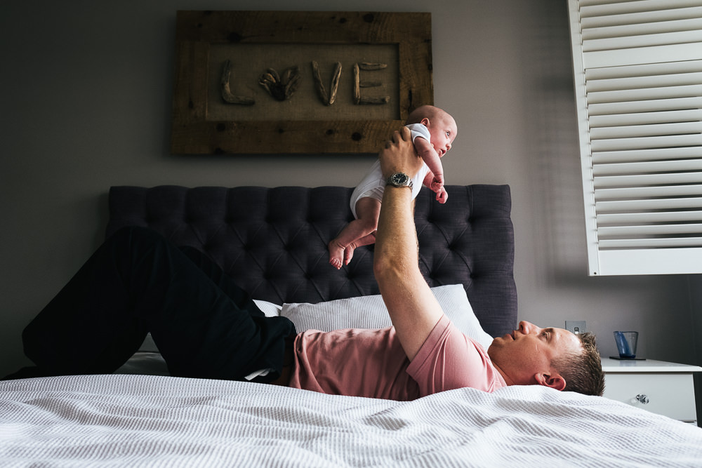 NEWBORN PHOTOGRAPHER LONDON AND KENT DAD THROWING BABY IN AIR ON BED