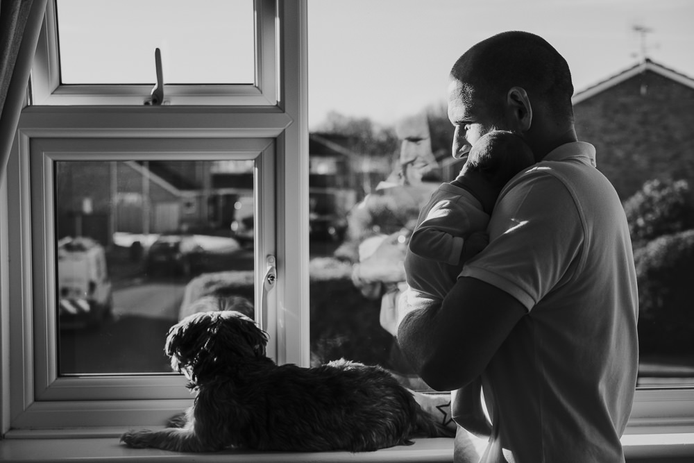 NEWBORN PHOTOGRAPHER LONDON AND KENT BLACK AND WHITE FATHER BABY AND DOG PORTRAIT WINDOW
