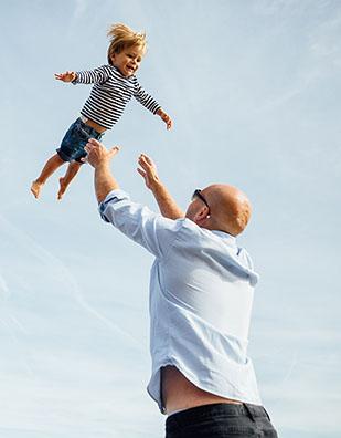MAN THROWING TODDLER BOY SON IN AIR ON BEACH BLUE SKY