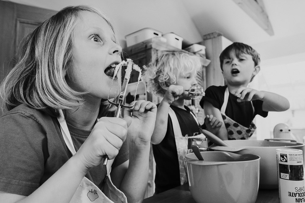 day in the life photographer children baking and licking cake mix from beaters black and white photo