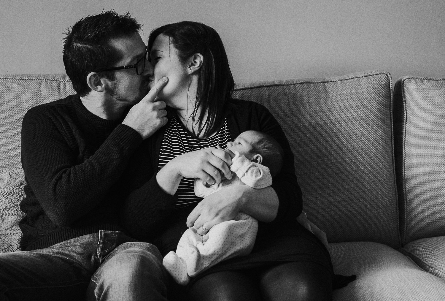 tunbridge wells baby photographer parents and newborn on sofa black and white kissing