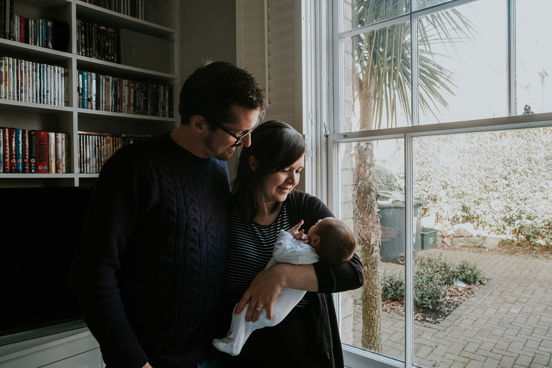 tunbridge wells baby photographer parents with newborn standing by window hugging