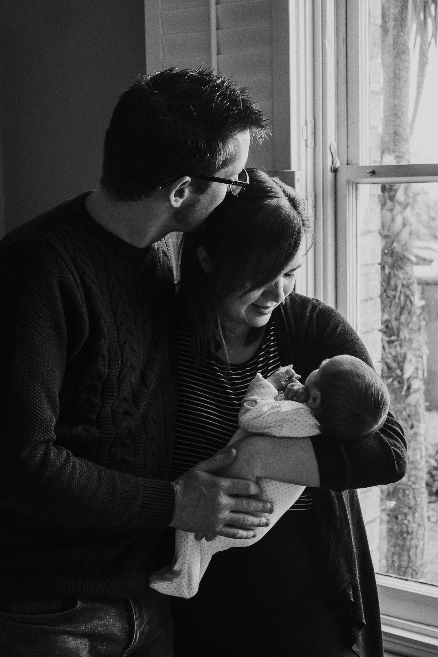 tunbridge wells baby photographer parents with newborn standing by window hugging black and white