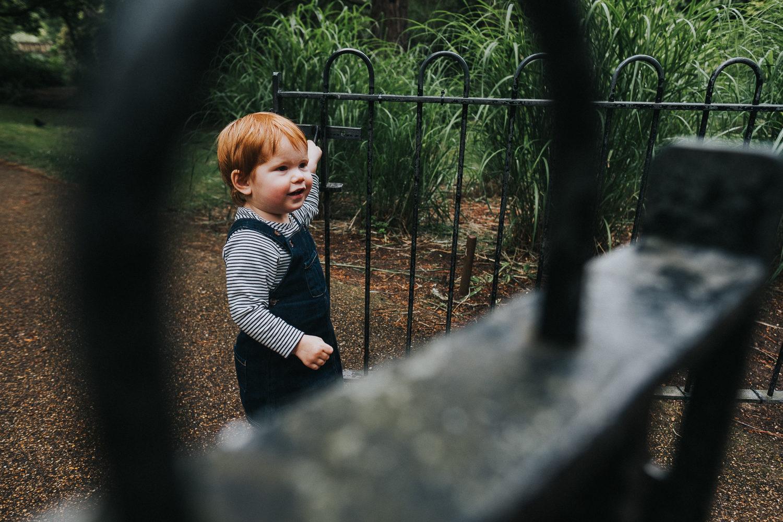 peckham family photo shoot park photography in london little girl closing gate