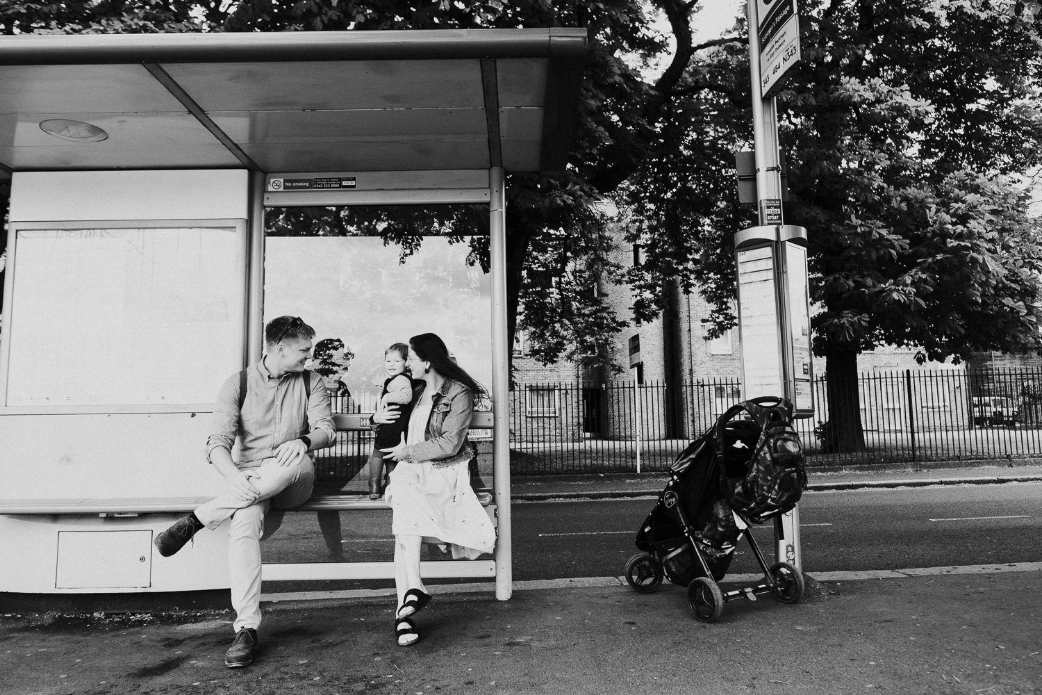 family two adults and baby waiting at bus stop black and white peckham london