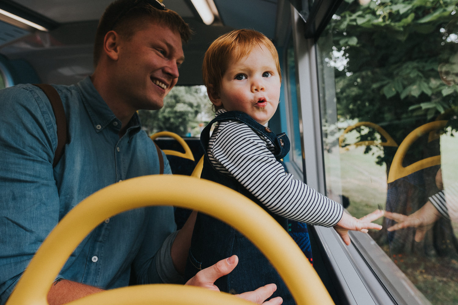 little toddler girl and father on top deck of london bus in peckham