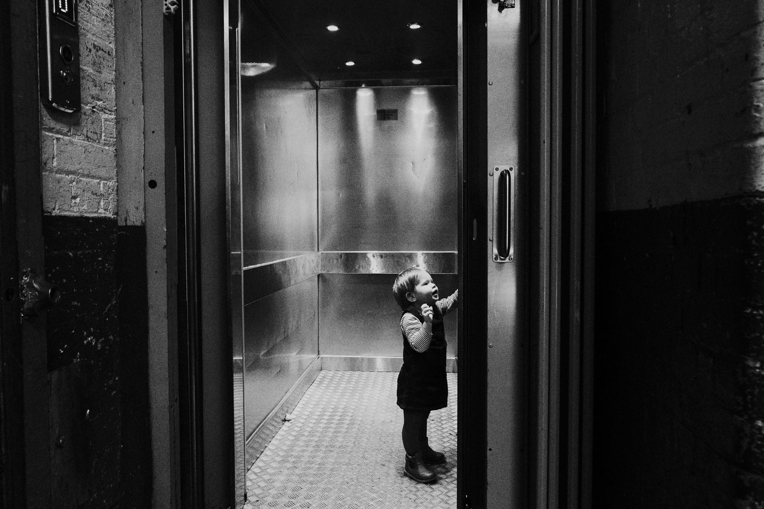 black and white shot of little toddler girl alone in lift pressing buttons